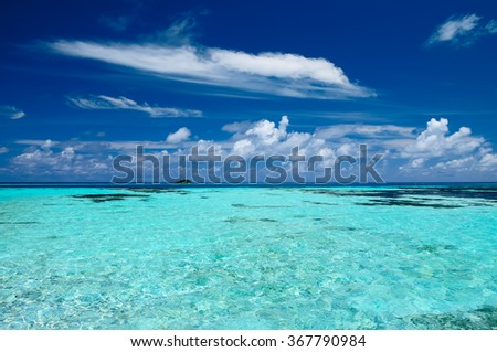 Tropical seascape of the fresh turquoise sea water, deep blue sky and white clouds in Maldives. - stock photo