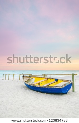 Tropical Seascape with a wooden, old and broken yellow blue boat on white beach on sunset. - stock photo