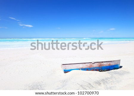 Tropical Seascape with an wooden, old and broken boat on white and sunny beach under a blue sky. - stock photo