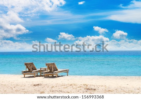 Tropical seascape with bamboo beach beds under blue sky