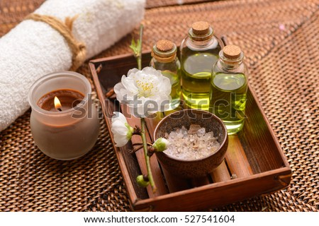 Tropical setting on mat with massage oil,candle,cherry,towel