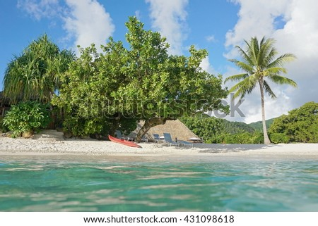 Tropical shore near a resort with a kayak and lounge chairs on the beach, seen from water surface, Fare, Huahine island, south Pacific, French Polynesia - stock photo