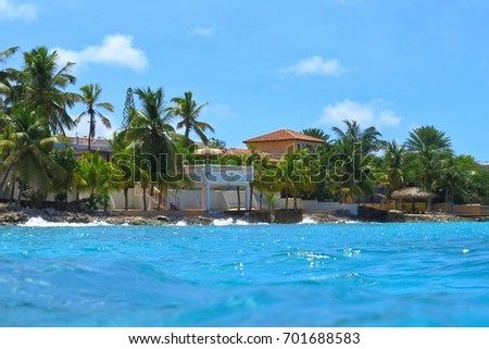 Tropical shore with blue sea, houses and coconut palm trees. Exotic island coastline with tropical ocean, view from water.