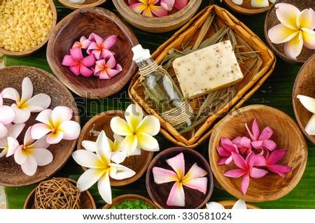 tropical spa with colorful salt and colorful frangipani on leaf   - stock photo