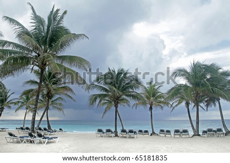 Tropical storm on an empty white sand beach, ocean and palm trees in Mexico, Riviera Maya - stock photo
