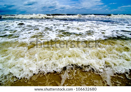 Tropical storm waves crashing on the coast with storm clouds above. - stock photo