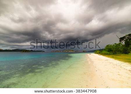 Tropical stormy weather in the remote Togean Islands, Central Sulawesi, Indonesia. From the white sandy beach to the blue lagoon, with scenic clouds, islets and fishermen village in the background. - stock photo