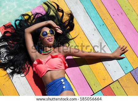 Tropical summer holiday fashion concept - tanning woman on a wooden pier - stock photo
