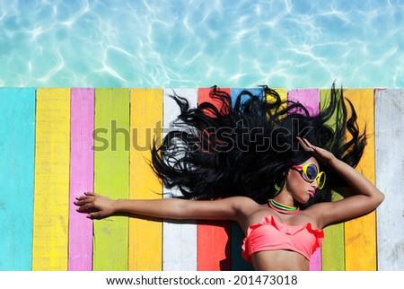 Tropical summer holiday fashion vogue concept - african american woman wearing sunglasses on a wooden pier background  - stock photo