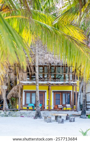 Tropical summer villa view through palm trees with beautiful colorful decor, lounges, beach table and wooden chairs in front of it at exotic white sandy beach in the Caribbean sea on Holbox, Mexico - stock photo