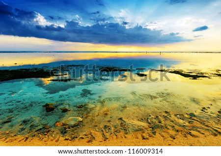 Tropical sunset at low tide. Gili Travangan island, Lombok, Indonesia. - stock photo