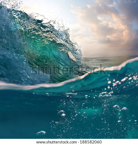 Tropical sunset background. Beautiful colorful ocean wave breaking closing near sand beach - stock photo