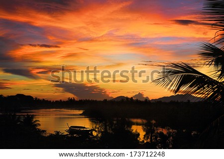 tropical sunset with big river - stock photo