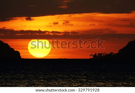 Tropical sunset with large sun - stock photo