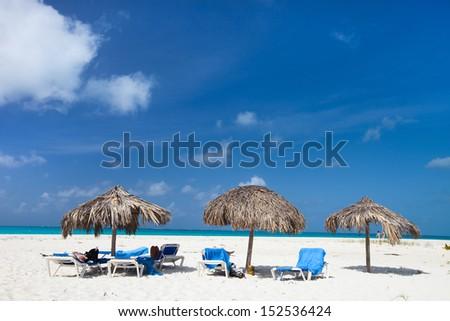 Tropical thatch umbrellas on a beautiful Caribbean beach  - stock photo