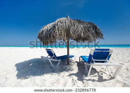 Tropical thatched umbrella on a beautiful Caribbean beach - stock photo