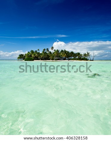 Tropical uninhabited or desert island with only a beach and palm trees in the famous Blue Lagoon inside Rangiroa atoll, an island of the Bora Bora archipelago French Polynesia in the Pacific Ocean.