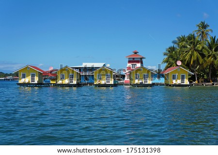 Tropical vacation bungalows over water with coconut trees on the Caribbean sea, Bocas del toro, Carenero island, Panama - stock photo