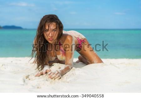 Tropical vacation. Young beautiful woman in bikini on the beach. - stock photo