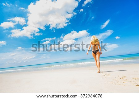 Tropical vacation. Young beautiful woman walking alone on the beach. Back view. Wide angle shoot.  - stock photo