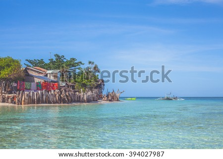 Tropical view of small traditional bamboo hut, hanging laundry, azure transparent water and clear blue sky. Mantigue Island, Philippines. Vacation and summer concept.