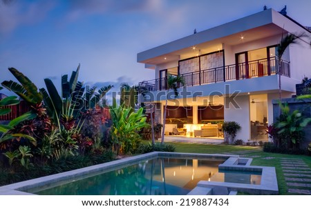 Tropical villa view with garden, swimming pool and open living room at sunset - stock photo