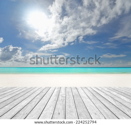 Tropical white sand beach with empty wooden platform - stock photo