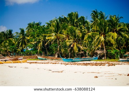 Tropical white sand beach with green palm trees and parked fishing boats in the sand. Exotic island paradise