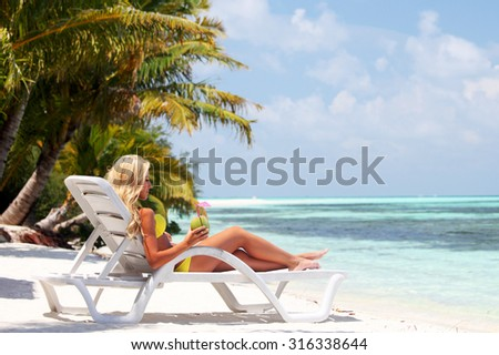 tropical woman on lounge with a coconut cocktail - stock photo