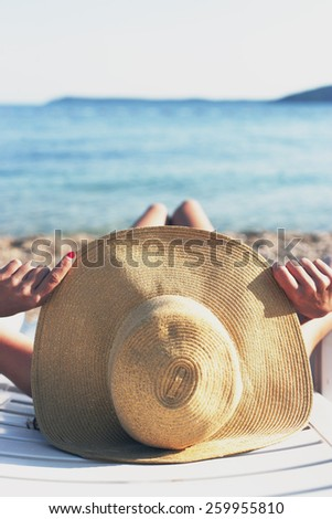 Tropical, woman sunbathing on the beach with hat - stock photo