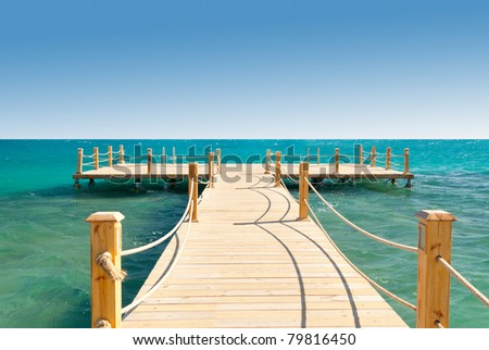 tropical wooden pier in turquoise sea at sunny weather, clear skies