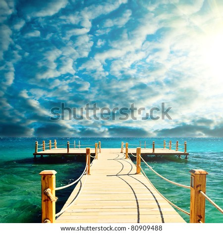 tropical wooden pier in turquoise sea stormy weather - stock photo