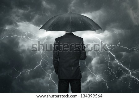 Trouble ahead concept, businessman with umbrella standing in the rain - stock photo