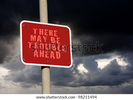 Trouble ahead sign against a dark cloud background - stock photo