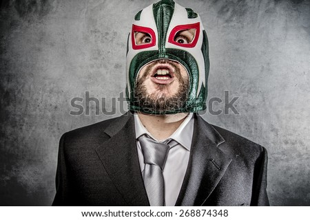 Trouble, businessman angry with Mexican wrestler mask - stock photo