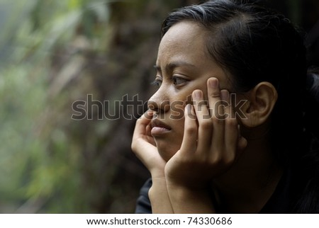 Troubled asian teen girl thinking with hands on face - stock photo