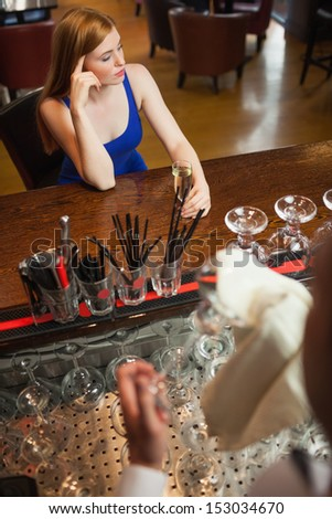 Troubled attractive woman having a flute of champagne alone in a classy bar - stock photo
