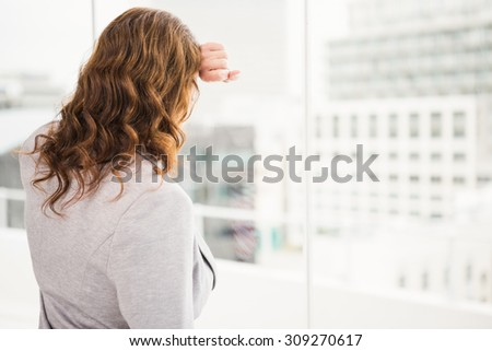 Troubled casual businesswoman leaning against window in the office
