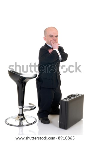 Troubled little businessman, dwarf in a formal suit with bow tie next to bar stool and suitcase, studio shot, white background - stock photo