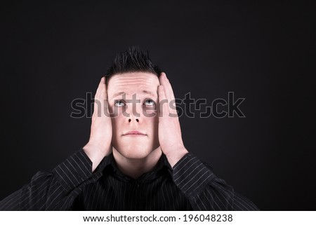 troubled man in black shirt with his hands on his face and looking up