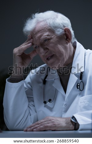 Troubled senior doctor sitting at the desk - stock photo