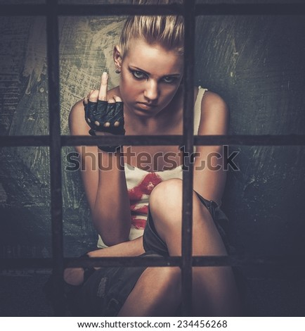 Troubled teenager girl behind bars showing middle finger  - stock photo