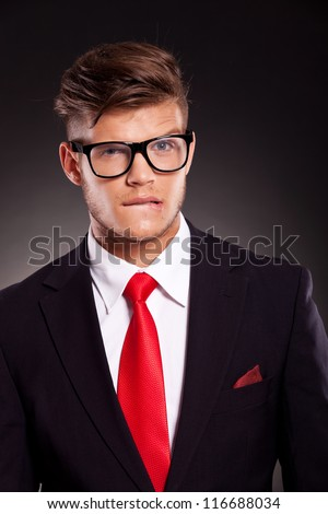 troubled young business man biting his lips and raising an eyebrow, over dark background