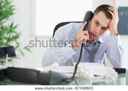 Troubled young businessman on the phone