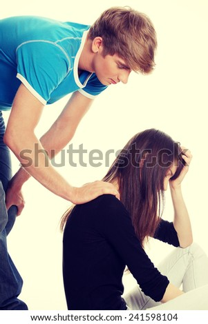 Troubled young girl comforted by her boyfriend.