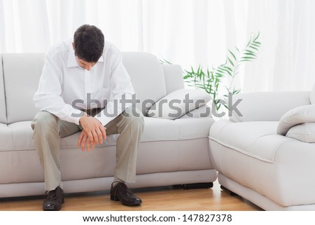 Troubled young man sitting on sofa lowering his head