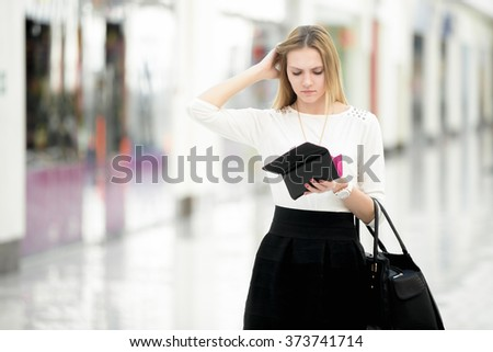 Troubled young woman looking perplexed into her wallet, spending money, limited budget, finance problems, copyspace - stock photo