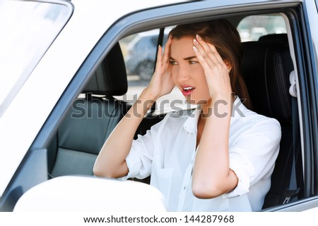 Troubles on the road, girl touches her forehead by hands while in a car - stock photo