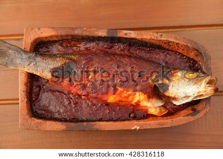 Trout fish baked in roof tile with tomato sauce. Horizontal shot - stock photo