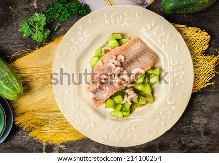 Trout with braised cucumber in plate on old wooden table wiht woven yellow cloth, top view - stock photo